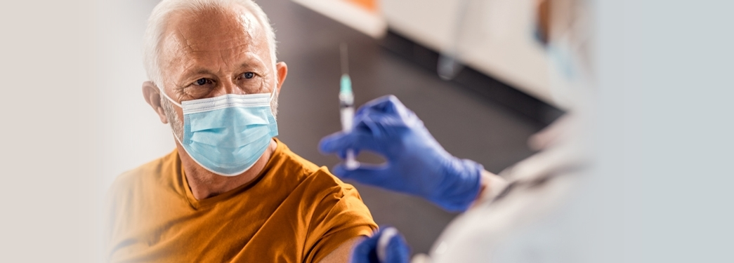 Elderly Man with mask About to get Syringe in arm